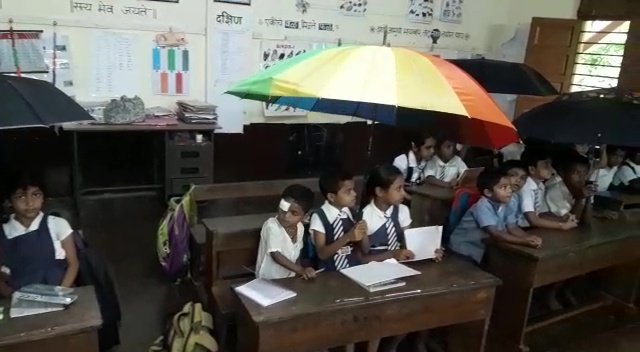 In Malcorne, students sit with umbrellas in the classroom